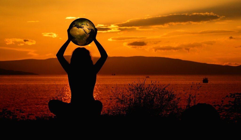 woman holding globe at sunset